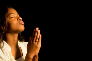 Young African-American woman praying with hands together